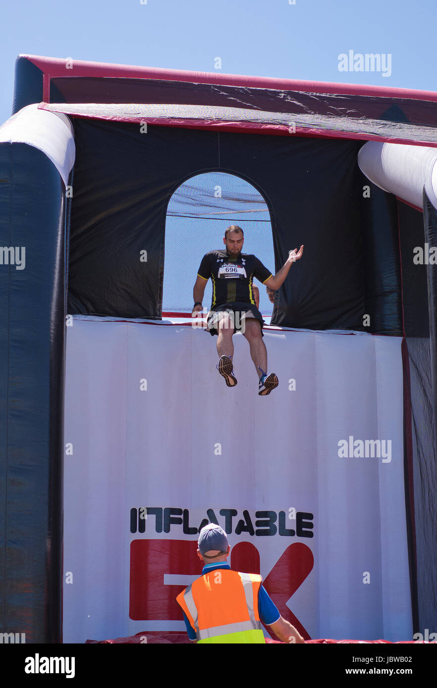 Man leaping off giant inflatable obstacle in Surrey England - Stock Image