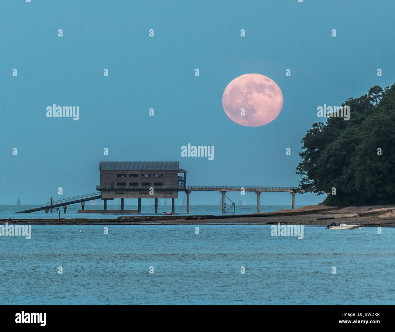 Full moon rising over Bembridge pier and lifeboat station - Stock Image