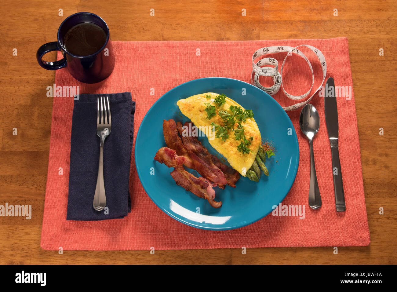 Horizontal food shot of asparagus omelet, bacon, coffee and a measuring tape - Stock Image