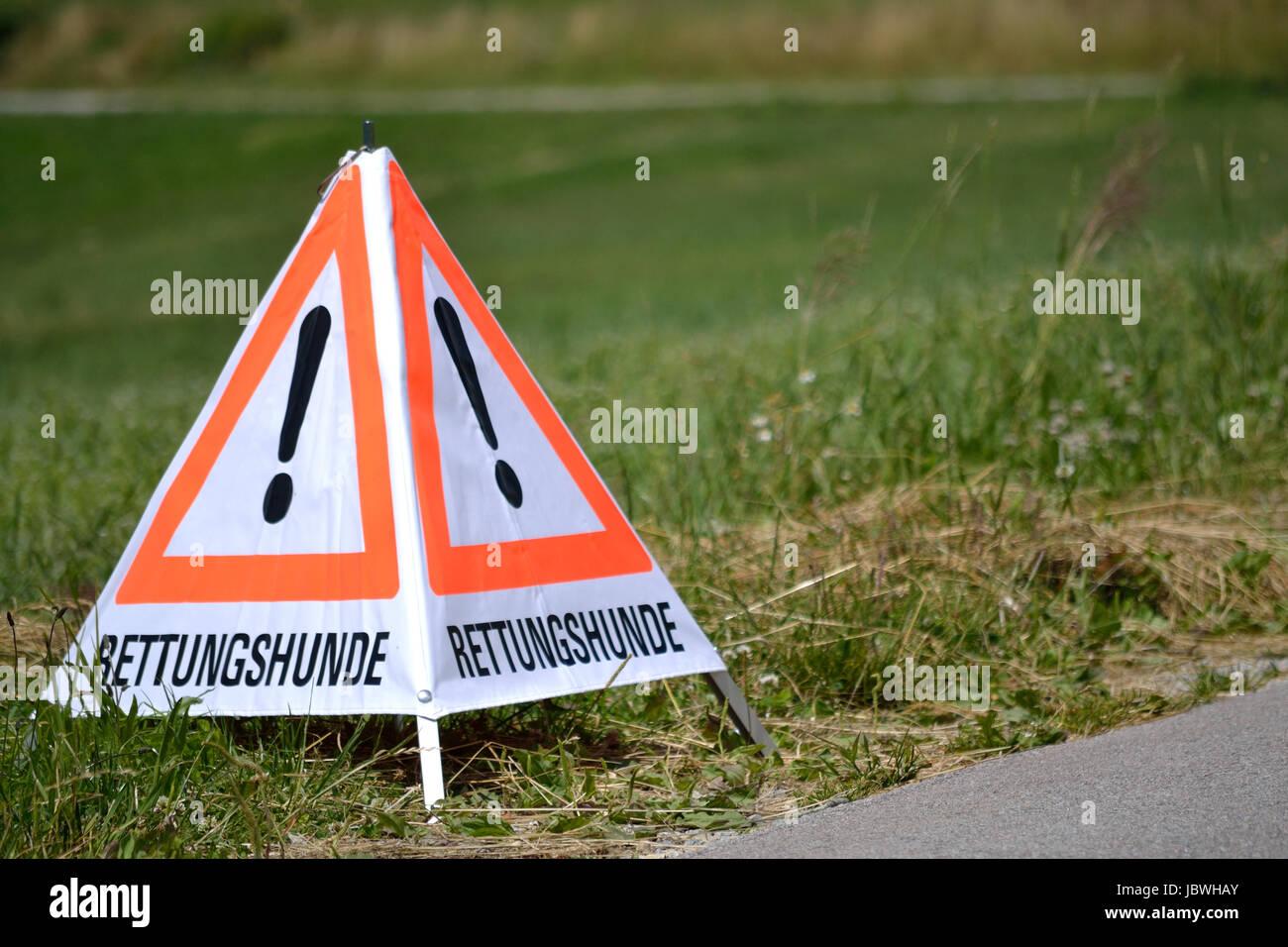 am Strassenrand aufgestelltes spezielles Warndreieck zwecks Rettungshundeeinsatz Stock Photo