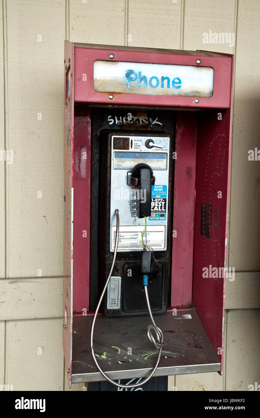 Abandoned coin operated public pay telephone with coin release slot, graffiti. - Stock Image