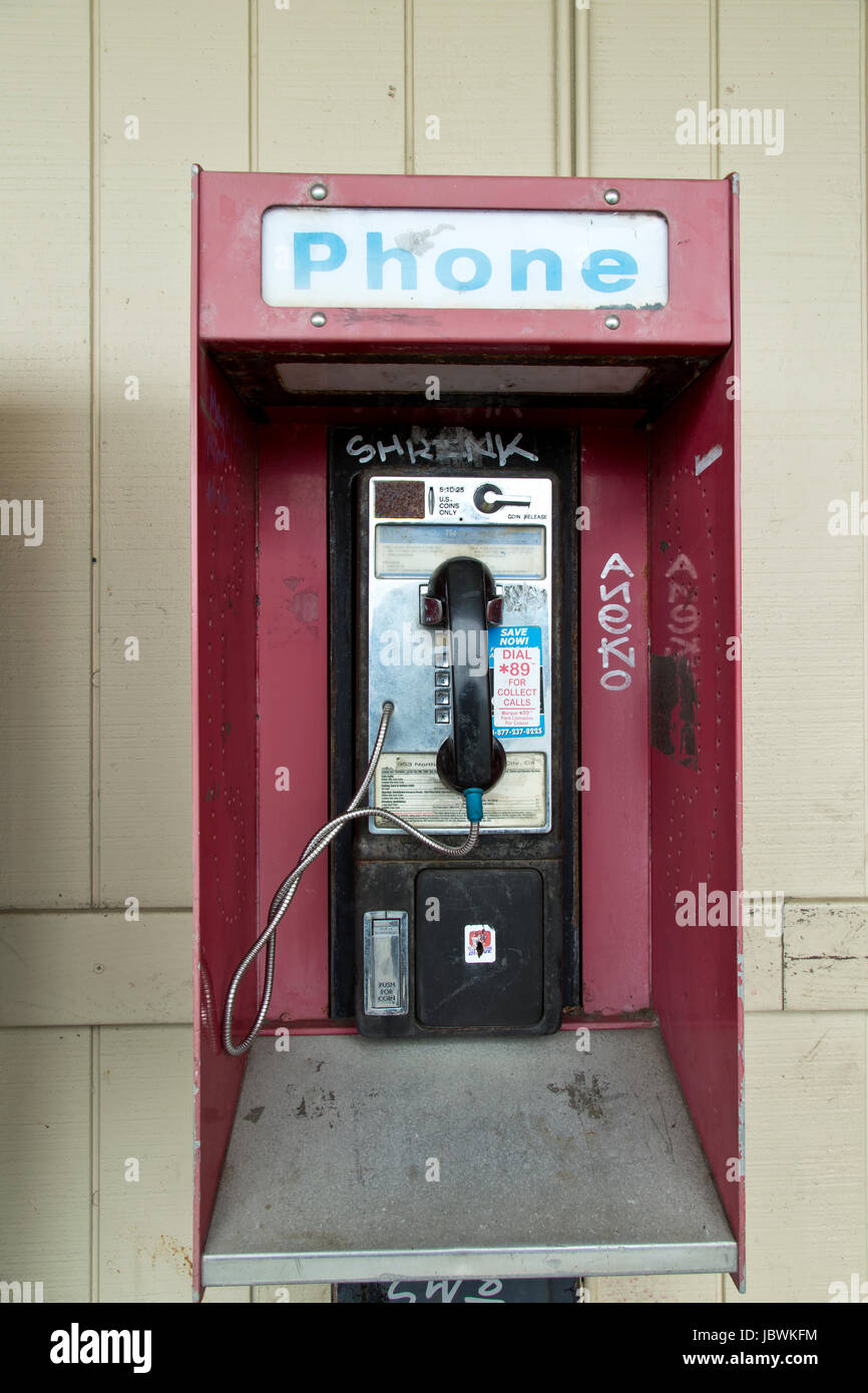 Abandoned coin operated public pay telephone with coin release slot, old shopping center, California, United States. - Stock Image