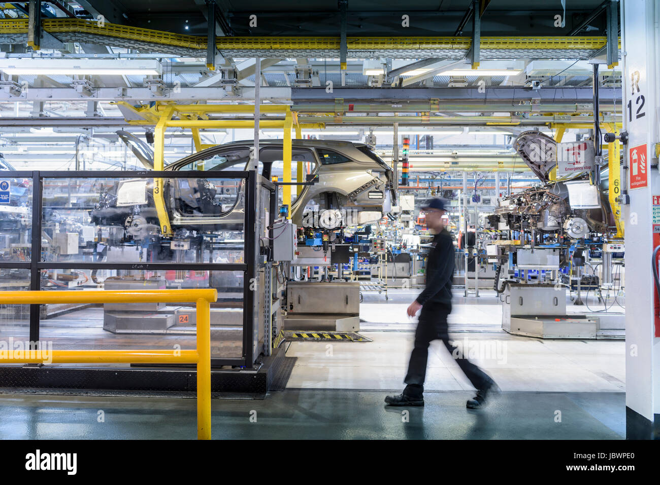 Engineer walking past car production line in car factory - Stock Image