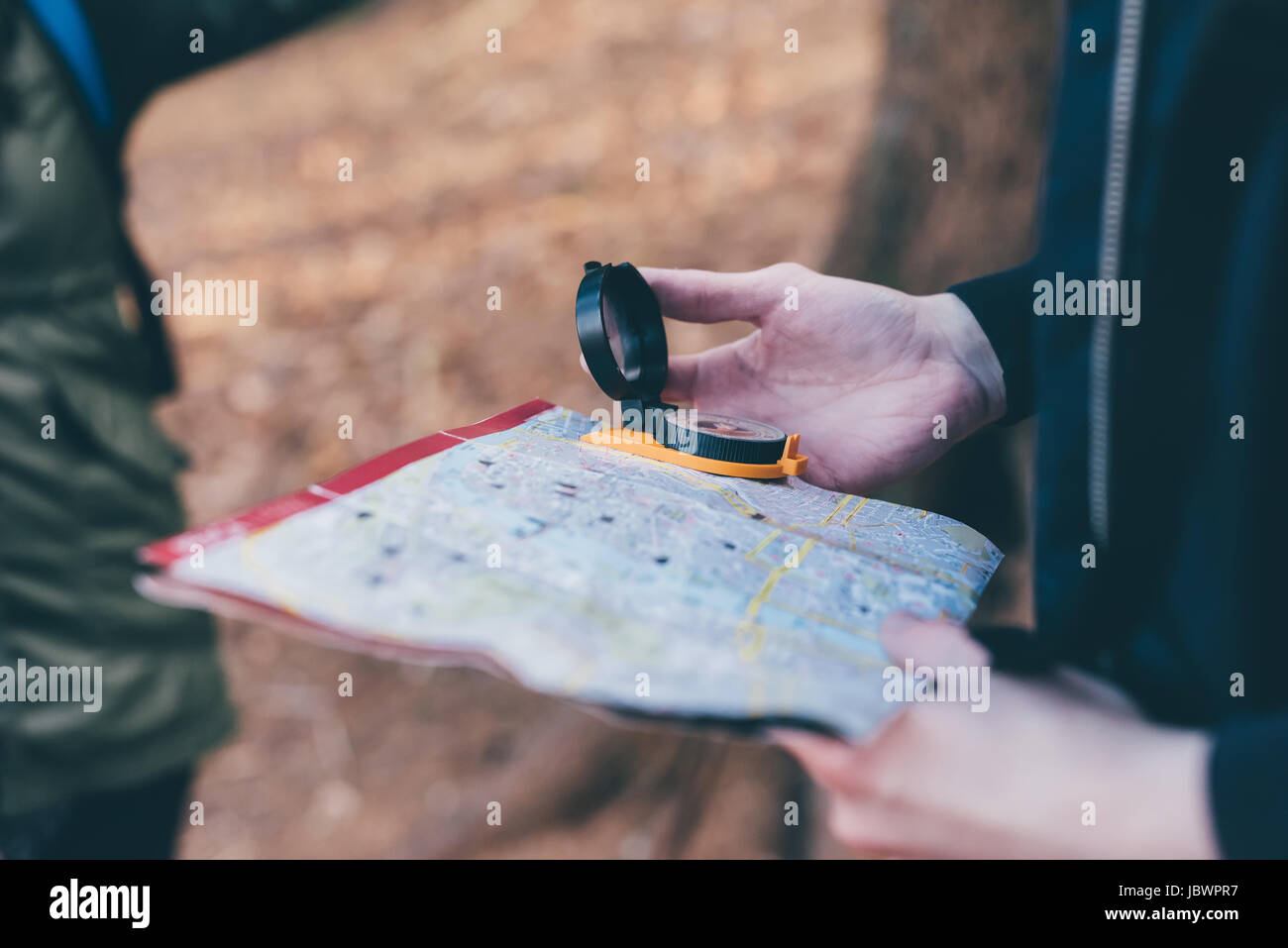 Cropped shot of hiking couple orienteering with compass and map, Monte San Primo, Italy - Stock Image