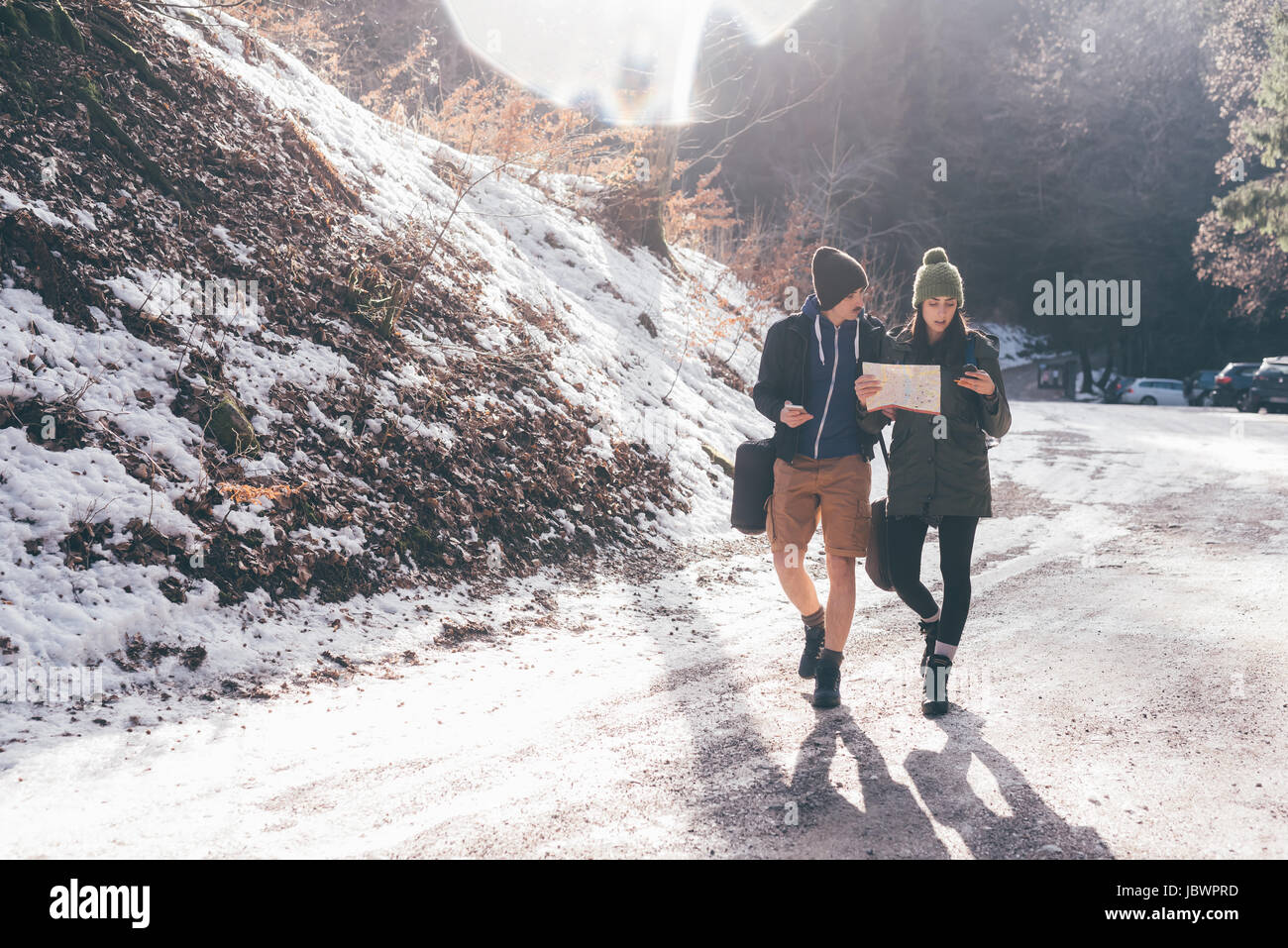 Hiking couple looking at compass hiking along rural road, Monte San Primo, Italy - Stock Image
