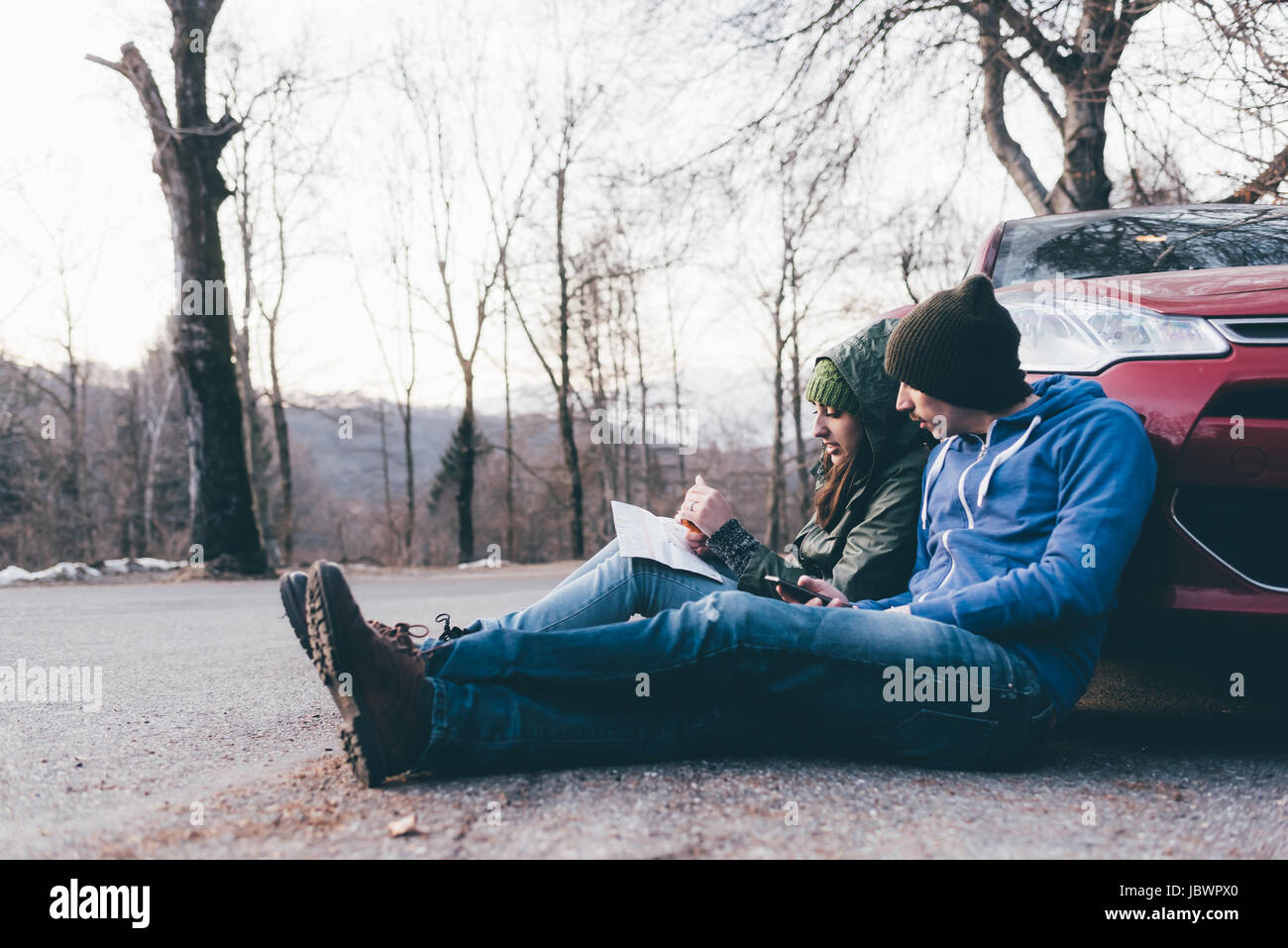 Hiking couple sitting on roadside looking at map, Monte San Primo, Italy - Stock Image