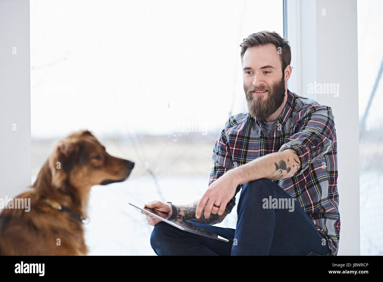 Young male designer with dog in design studio window seat - Stock Image