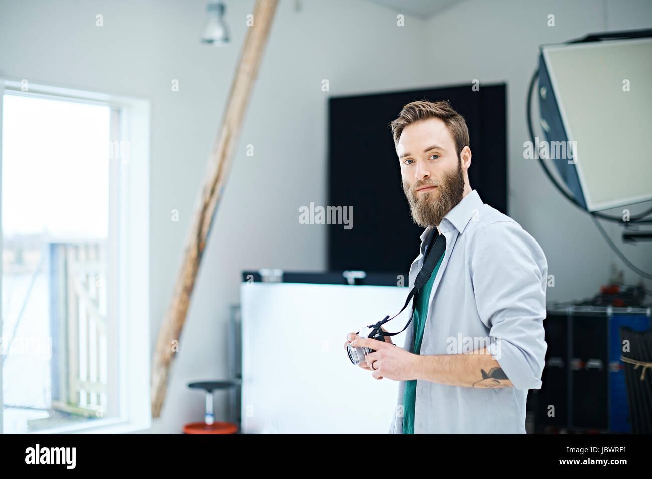 Portrait of male designer with digital camera in design studio - Stock Image