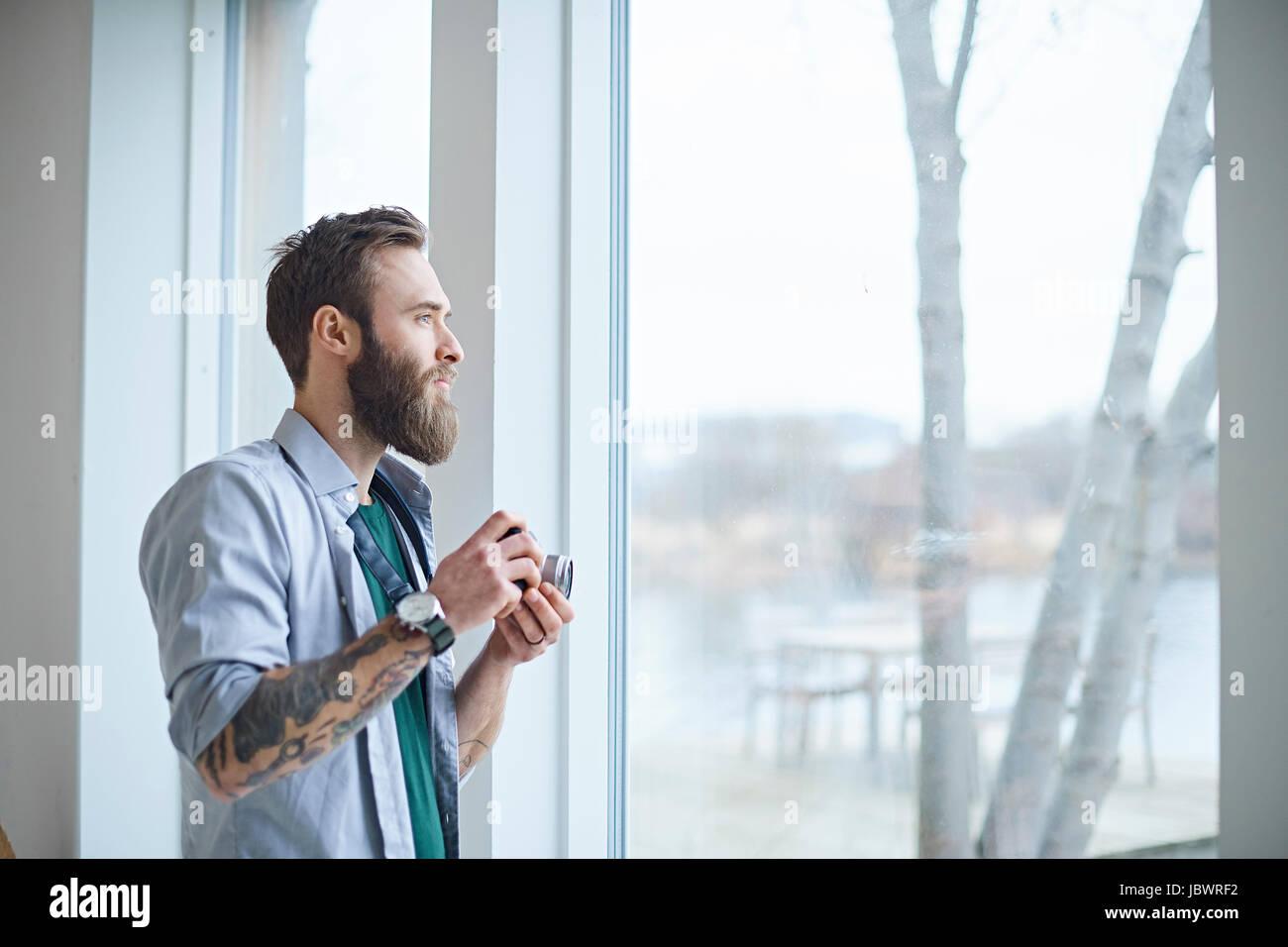 Male designer with digital camera looking through design studio window - Stock Image