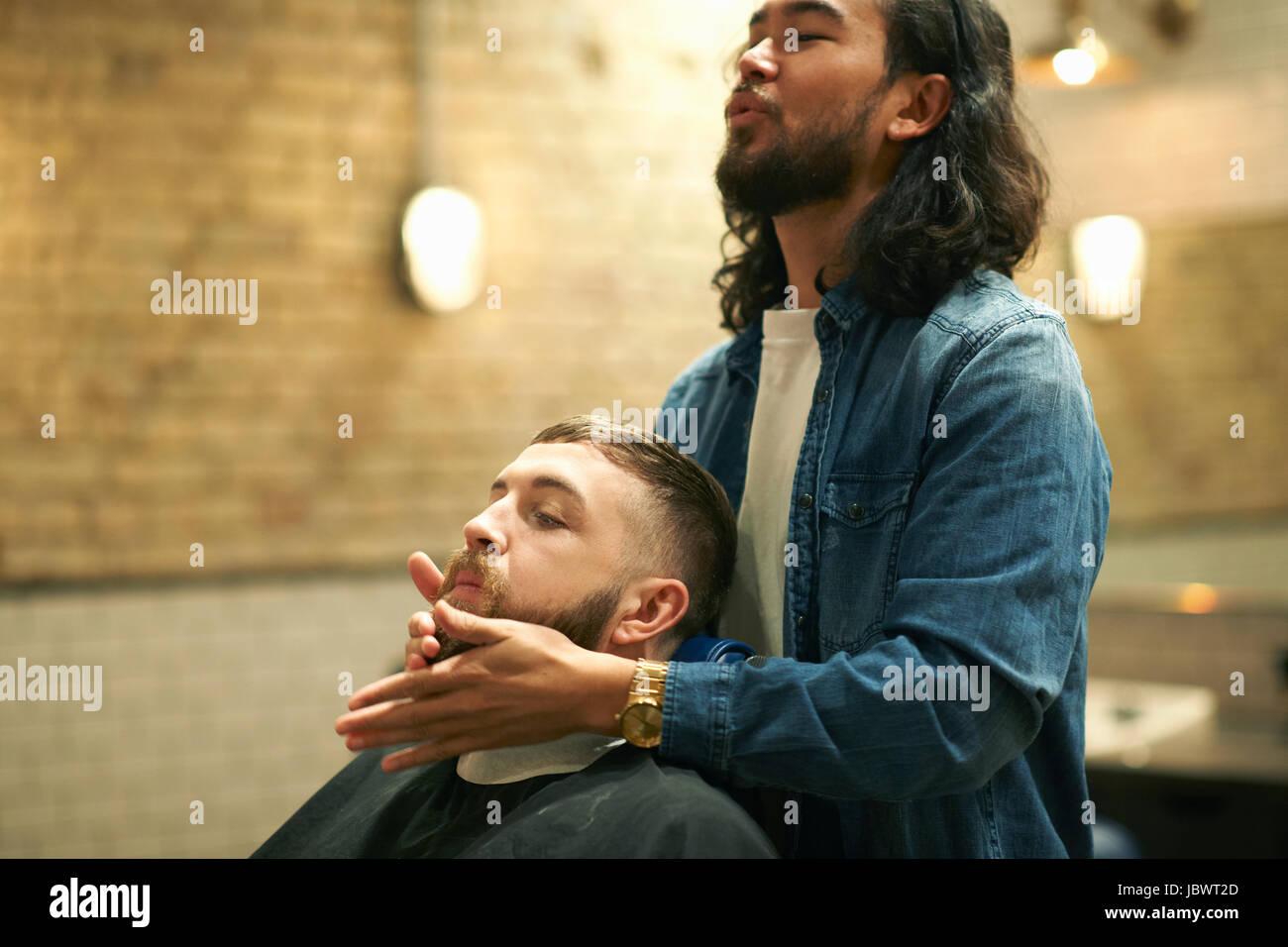Hairdresser in barbershop grooming customer's beard - Stock Image