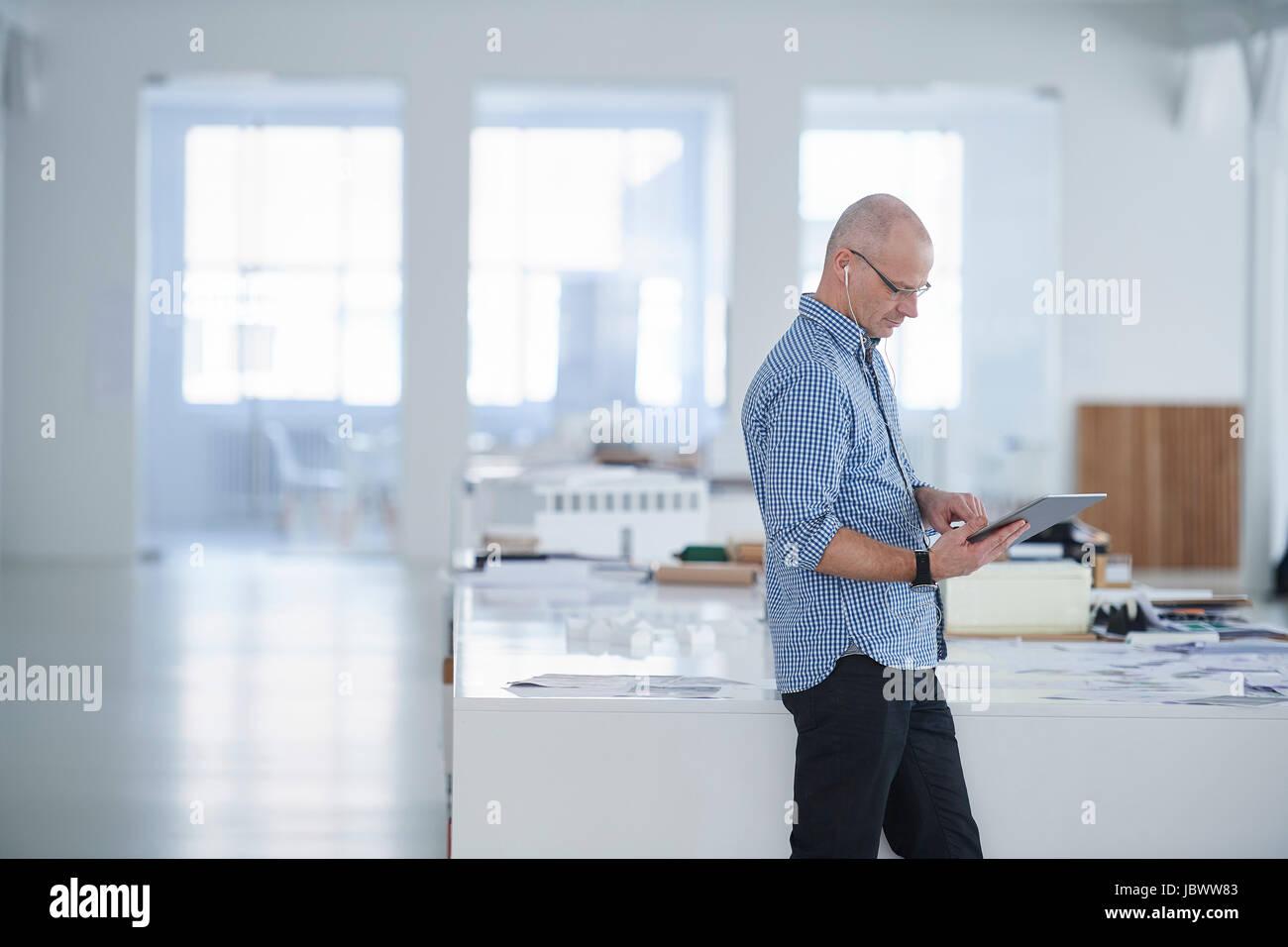 Man in open plan office using digital tablet - Stock Image