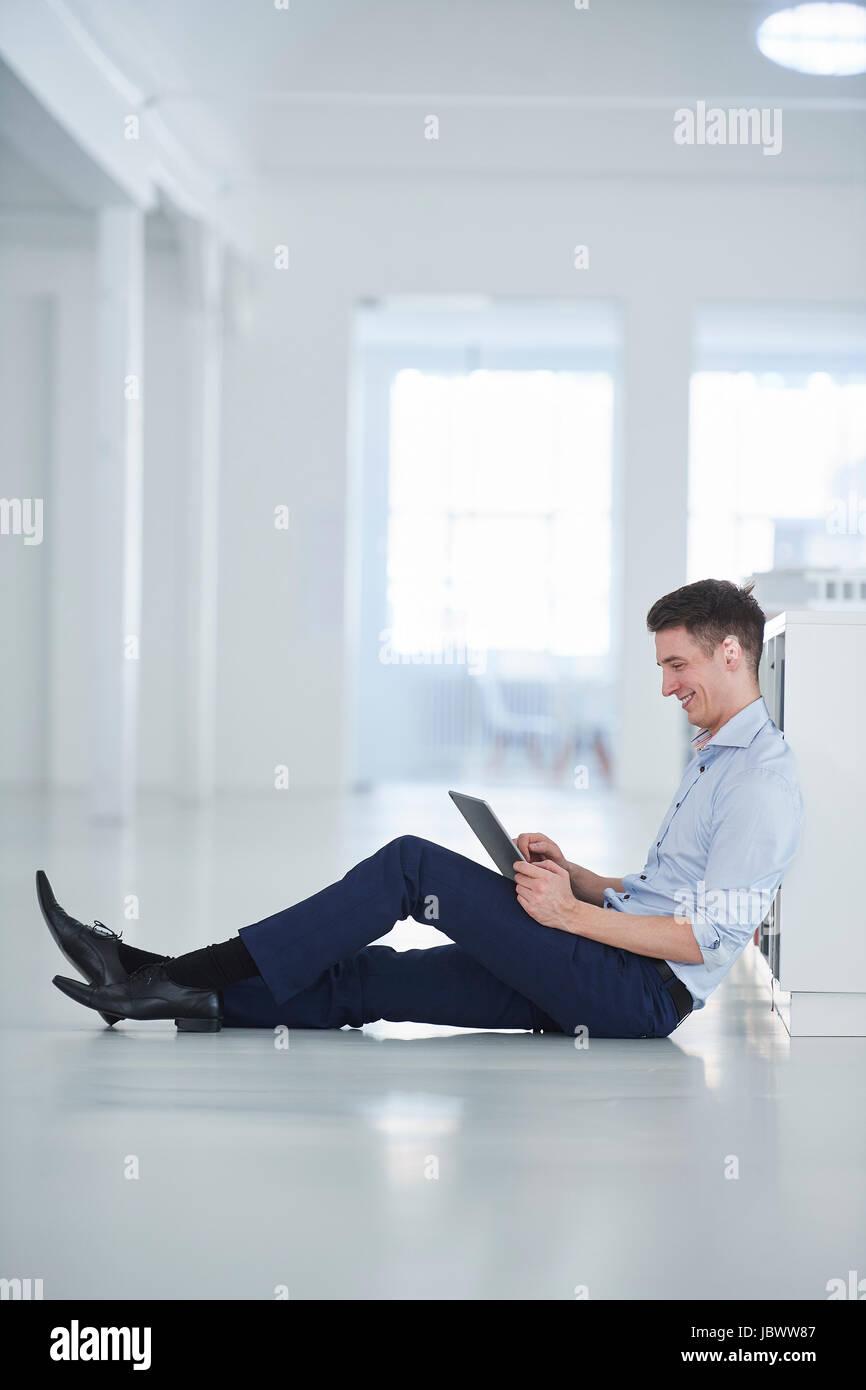 Man in office sitting on floor using digital tablet - Stock Image