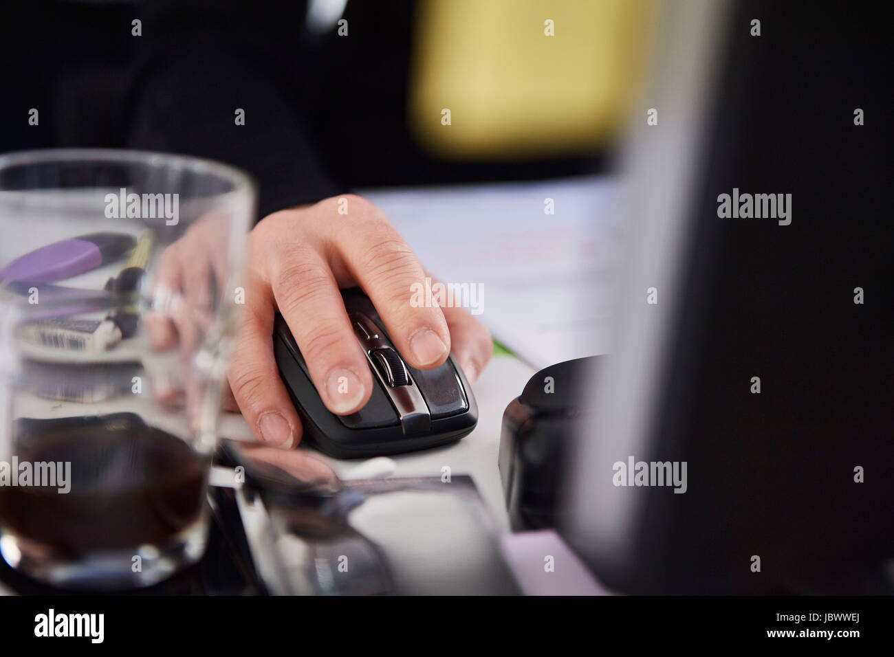Cropped view of woman using computer mouse - Stock Image