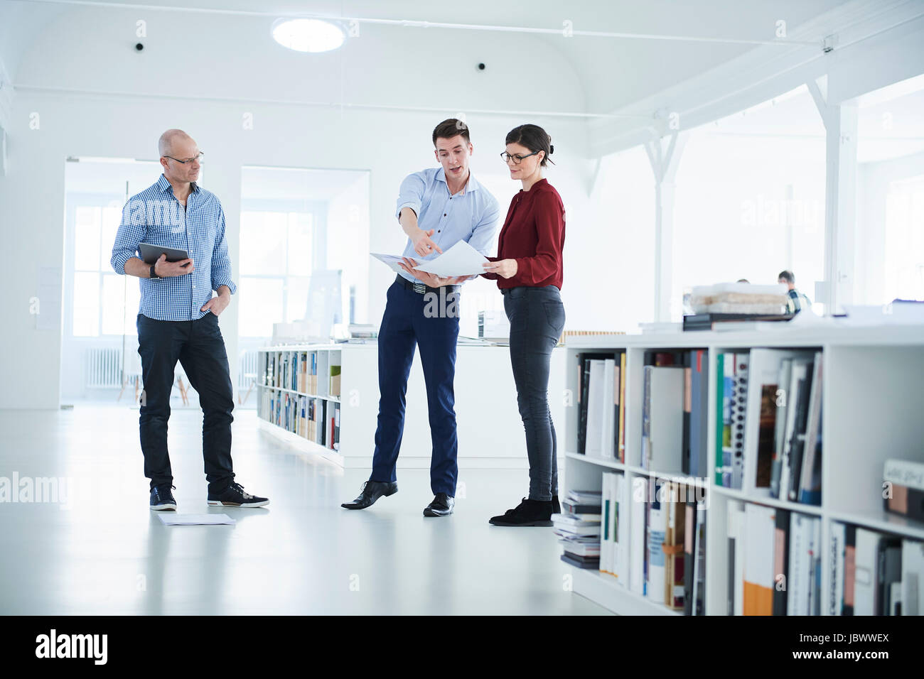 Colleagues discussing paperwork in open plan office - Stock Image