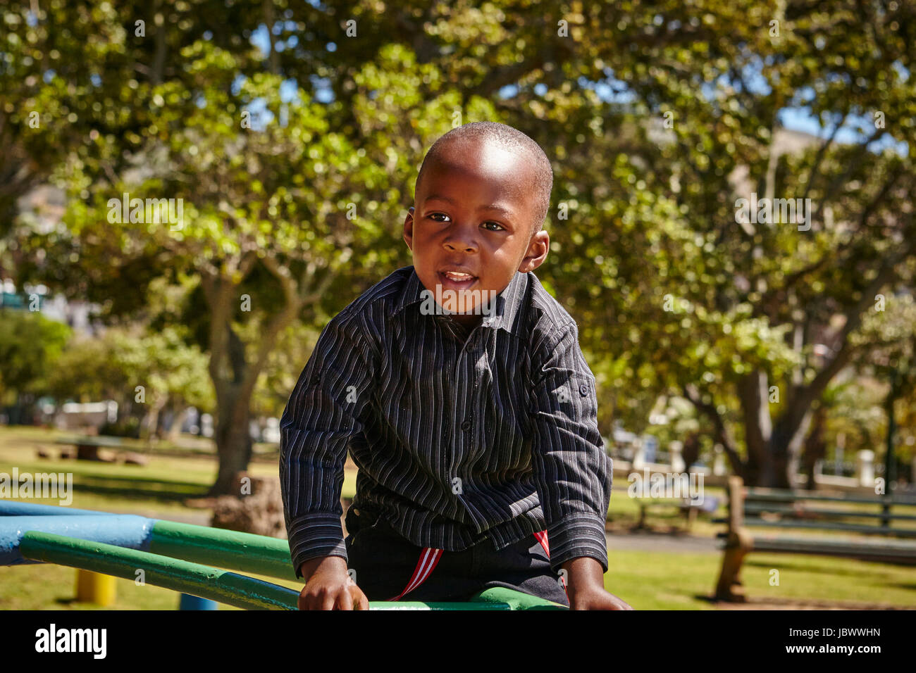 Boy on climbing frame in playground - Stock Image