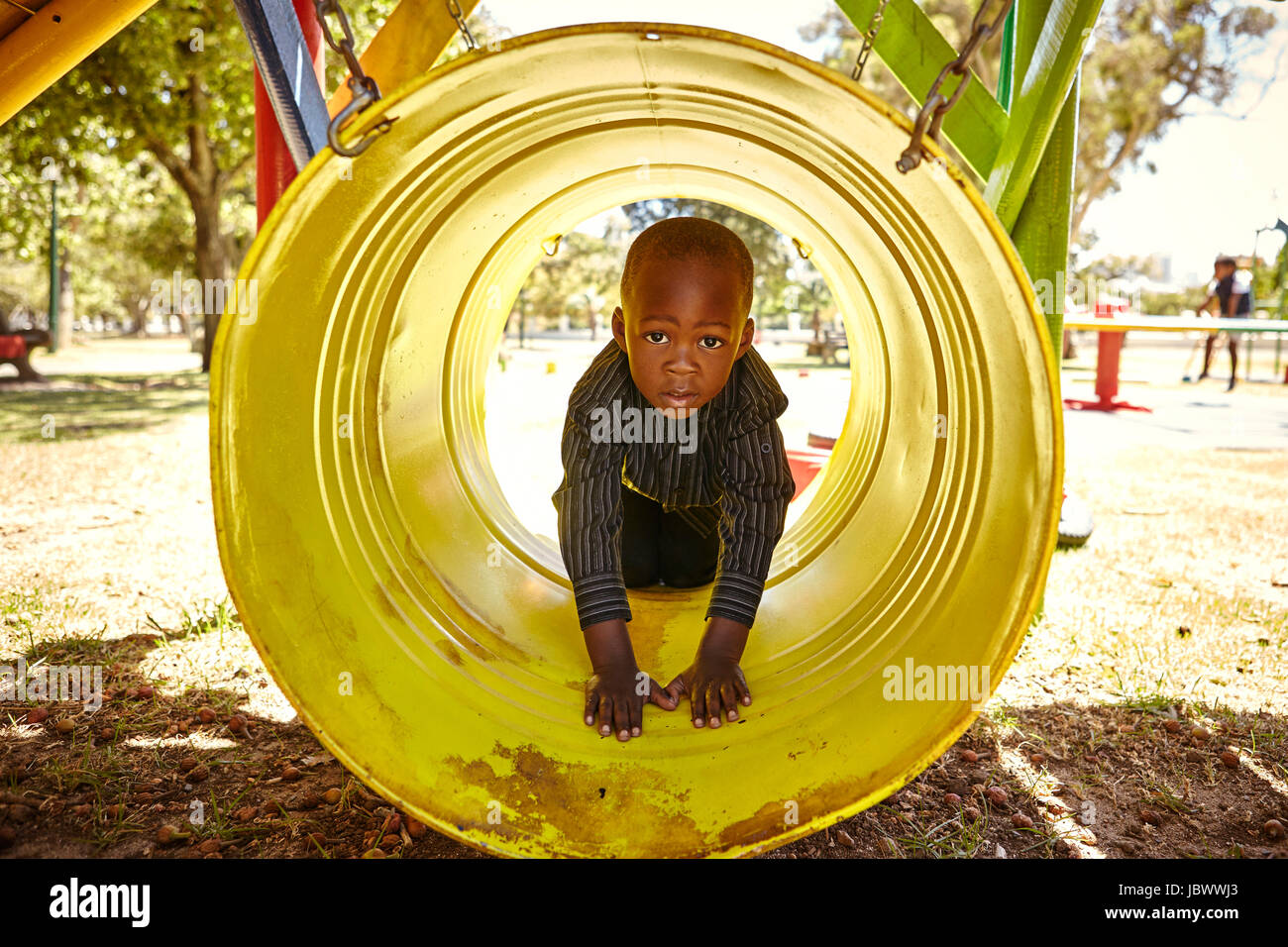 Boy in crawl tunnel in playground - Stock Image
