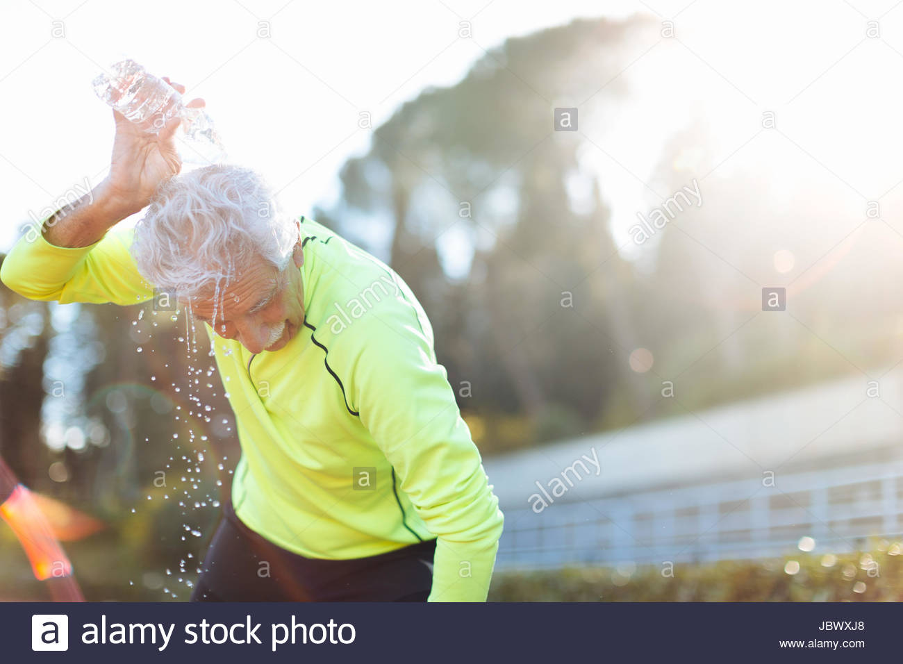 Senior man cooling off by pouring water over head - Stock Image