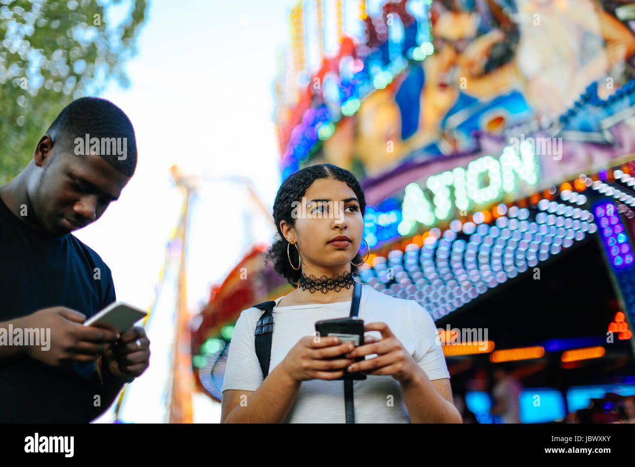Two friends at funfair, holding smartphones - Stock Image