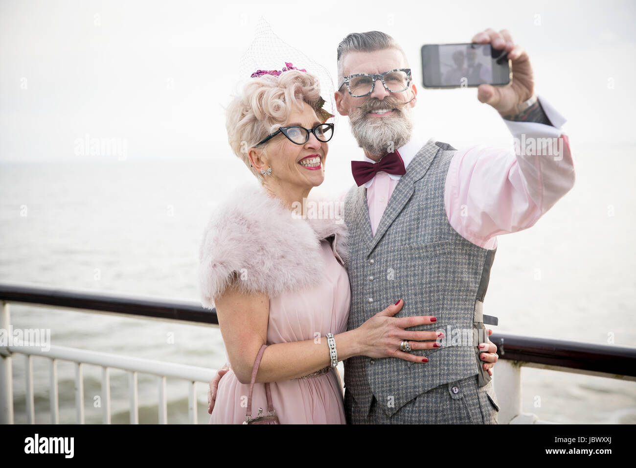 1950's vintage style couple taking smartphone selfie on pier - Stock Image