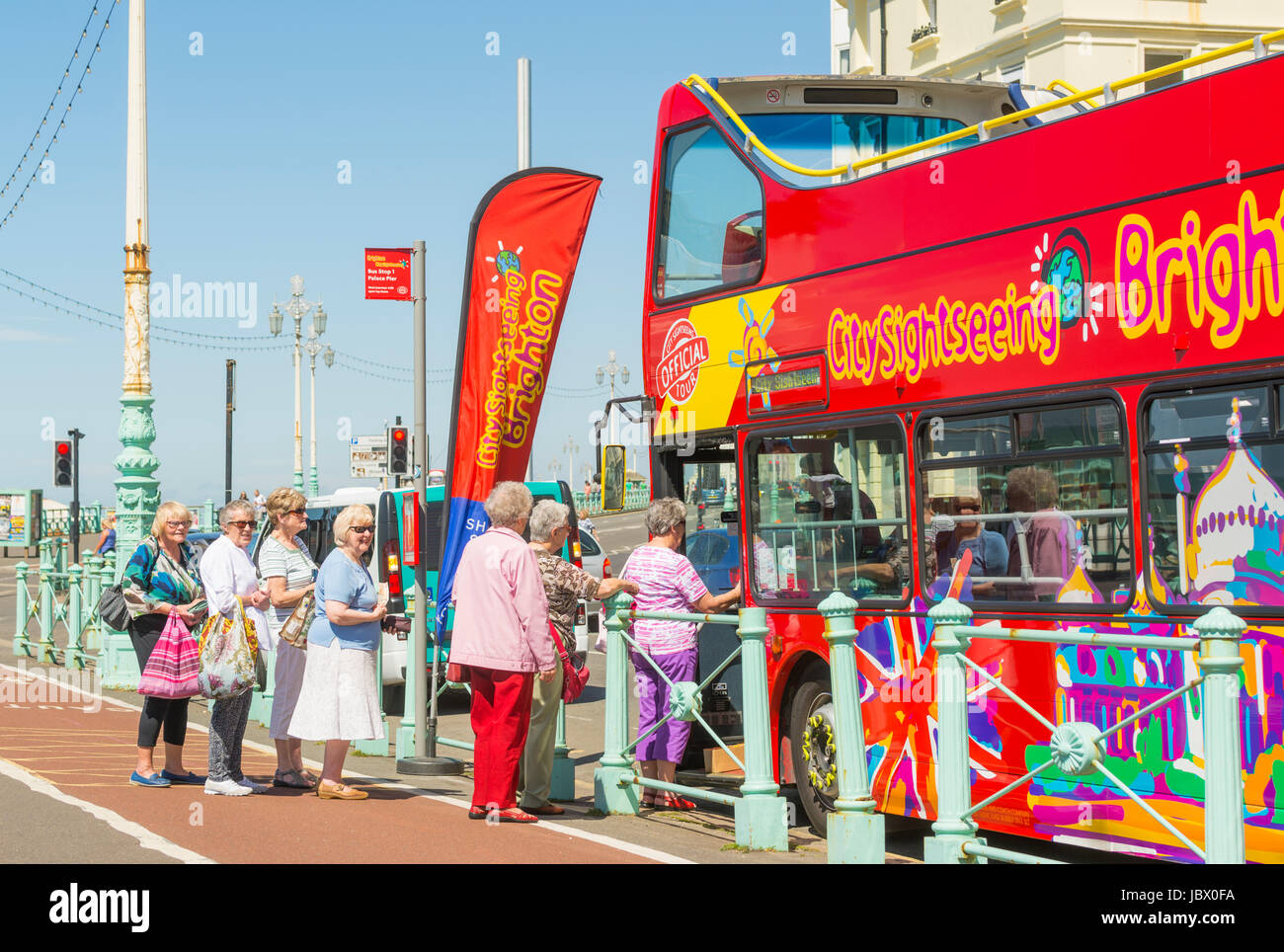 Sightseeing bus. Elderly tourists boarding the open top sightseeing bus on the seafront road in Brighton. East Sussex, - Stock Image