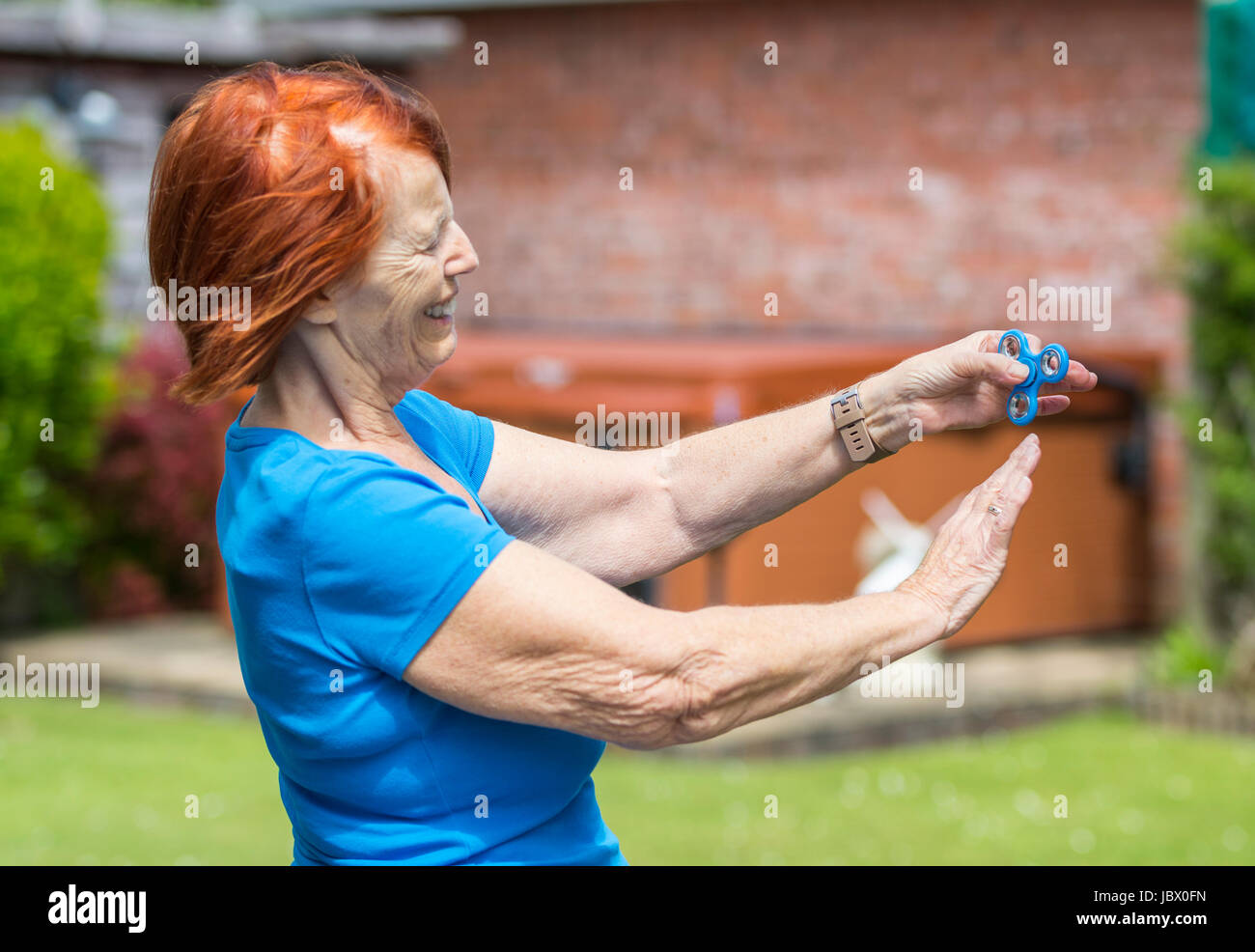 Elderly lady playing with a fidget spinner, the latest stress relieving craze - Stock Image