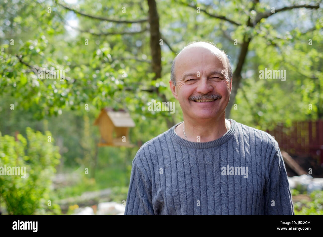Mature man sitting in garden near apple tree in countryside Stock Photo