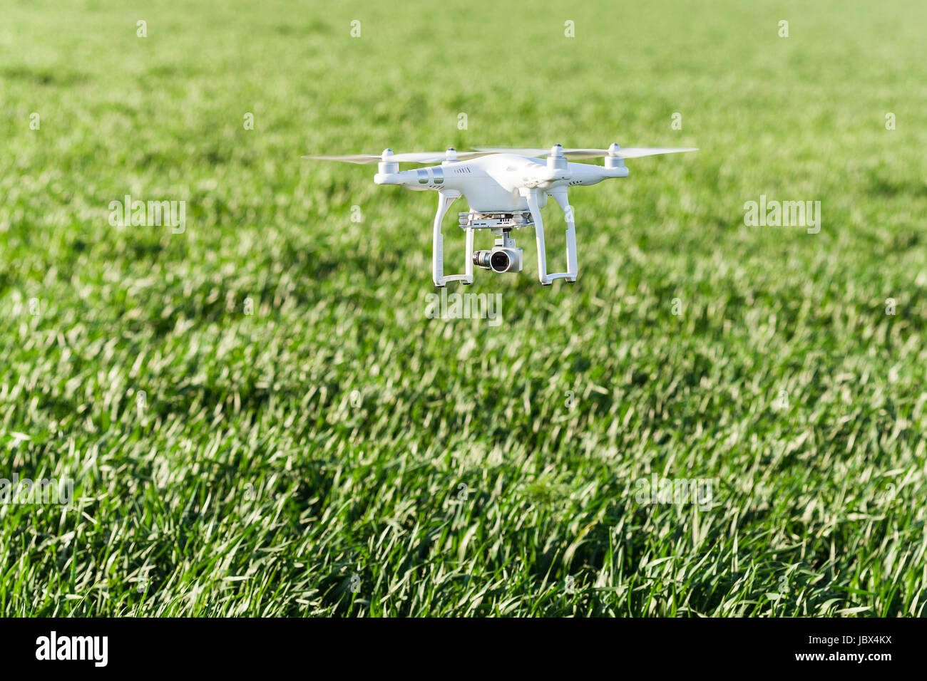 quadcopter outdoors, aerial imagery and recreation concept - low flying white drone with four propellers and build - Stock Image