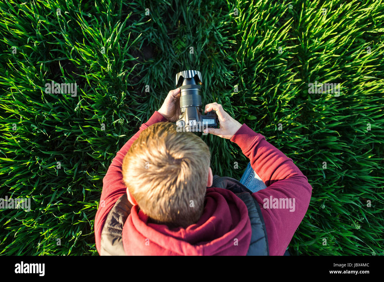 fascinating photography and process of shooting concept - top view of young male man with mirror camera in hands - Stock Image