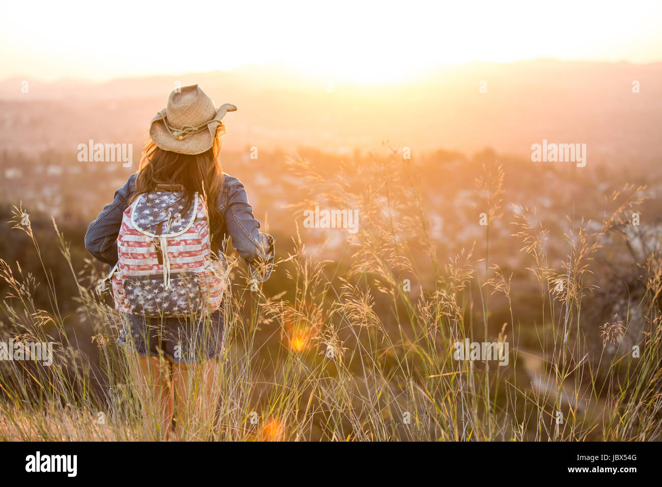Woman hiking, wearing stars and stripes backpack, rear view - Stock Image