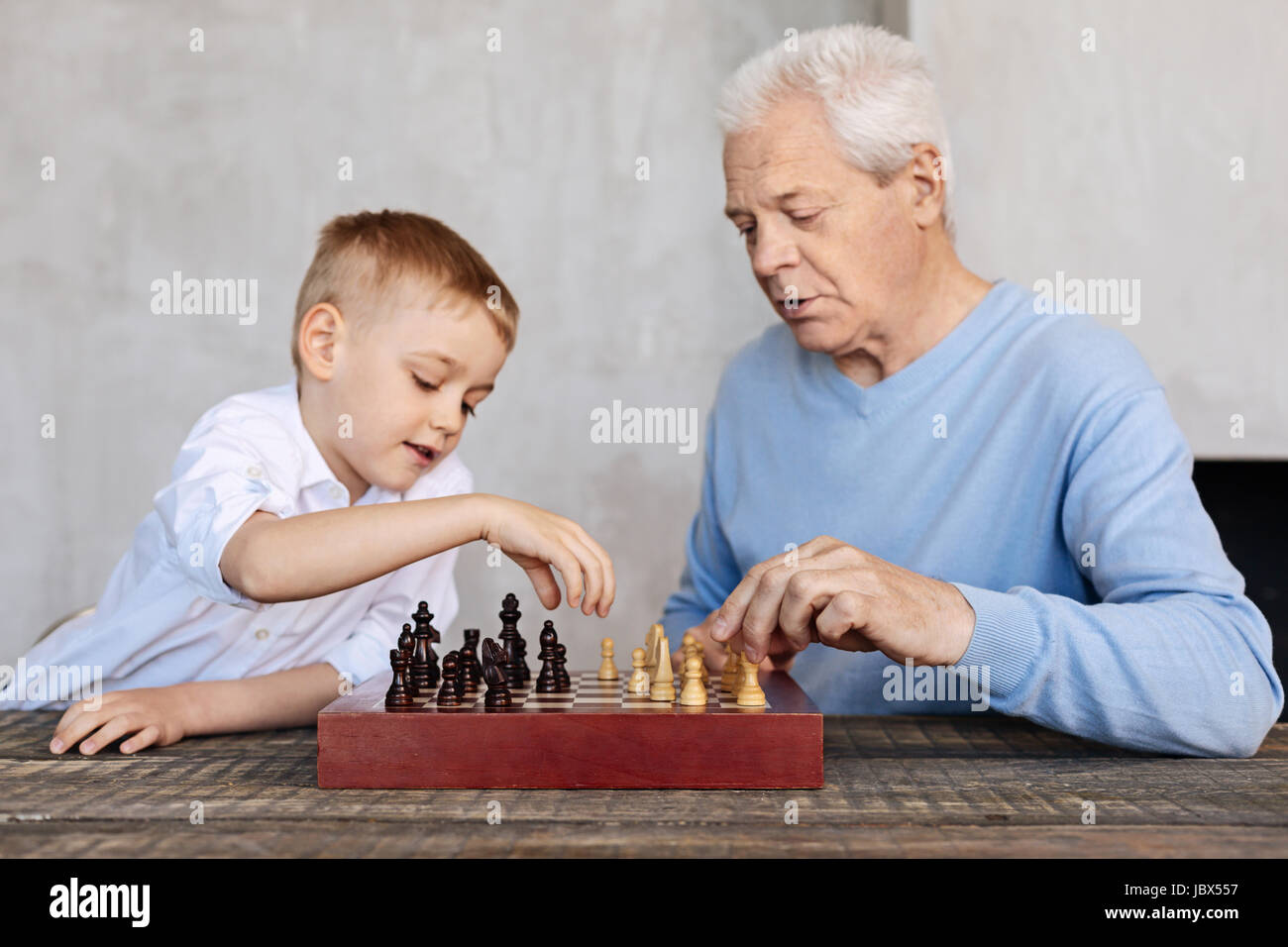 Cute kid and his grandparent playing chess - Stock Image