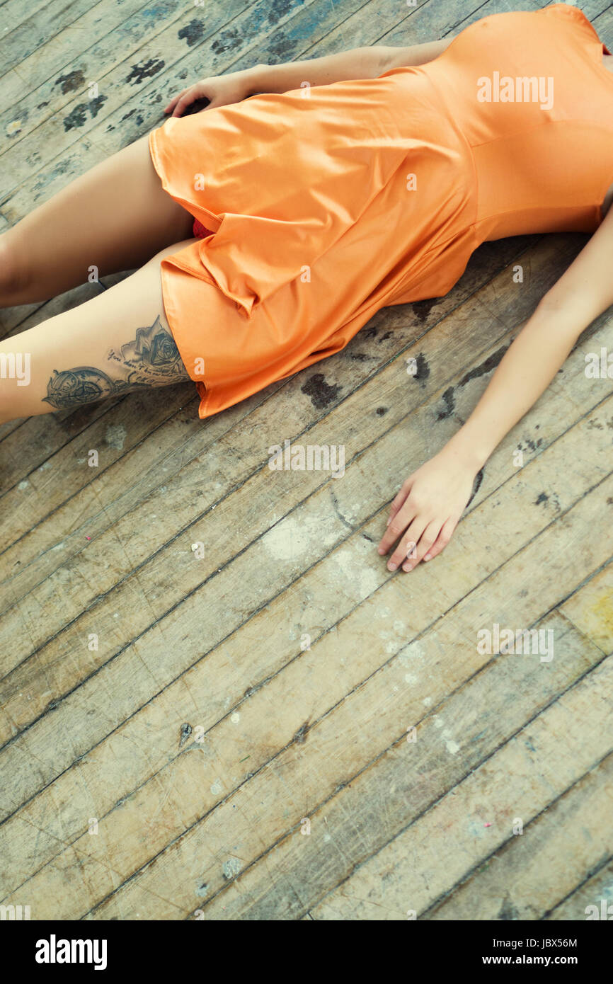 Dead woman's body laying down on the floor - Stock Image