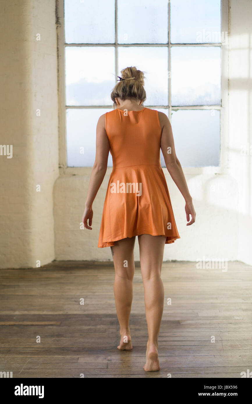 Rear view of a young blonde Caucasian woman wearing a short orange summer dress walking towards the window barefooted - Stock Image