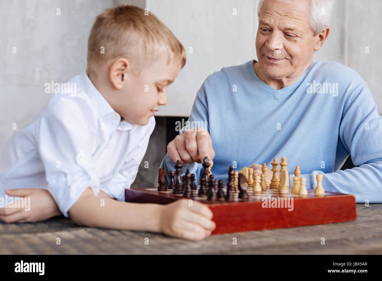 Excited lively man watching at grandsons reaction - Stock Image