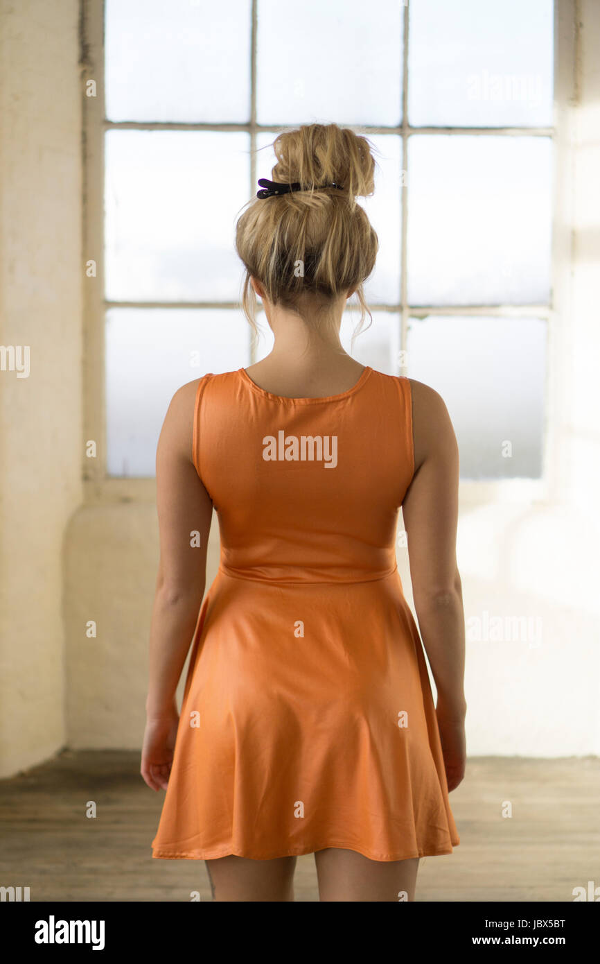 Rear view of a young blonde Caucasian woamn wearing an orange summer dress standing by the window - Stock Image