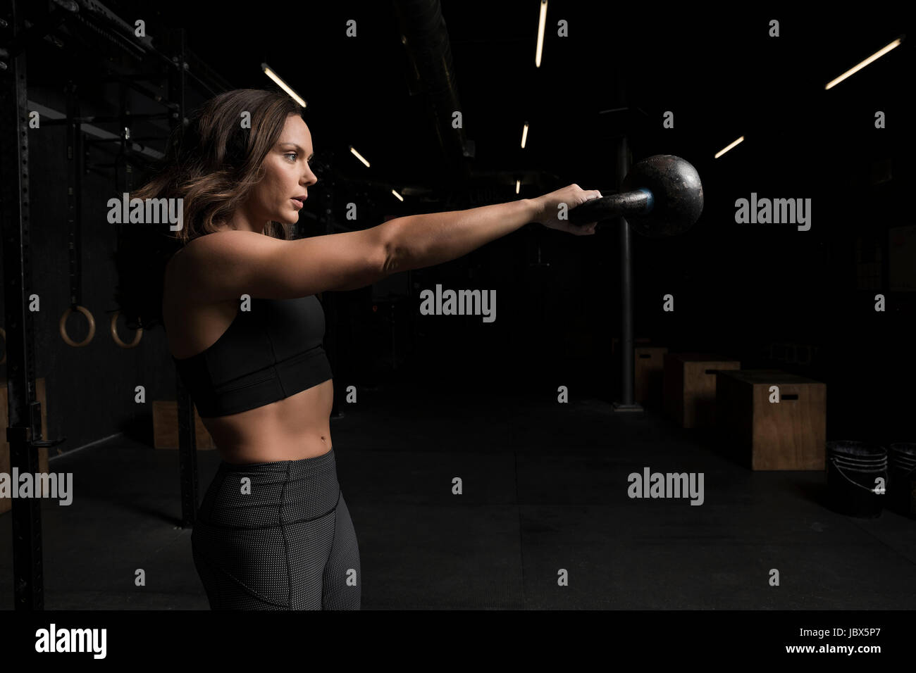 Young woman working out in cross fit gym - Stock Image