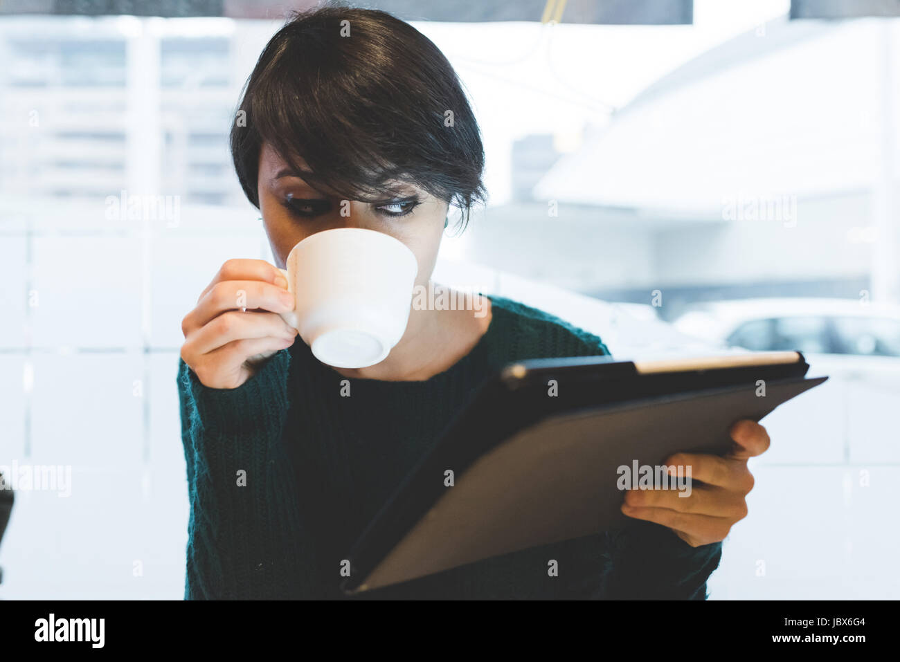Woman in cafe looking at digital tablet and drinking coffee - Stock Image