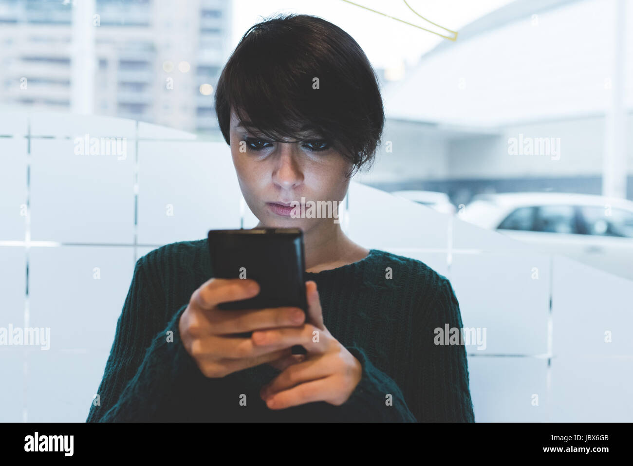 Woman in cafe looking at smartphone - Stock Image