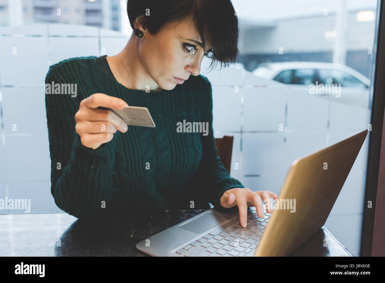 Woman in cafe making credit card payment on laptop - Stock Image