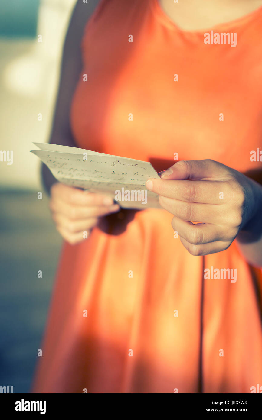 Close up of a young woman's hands holding a letter - Stock Image