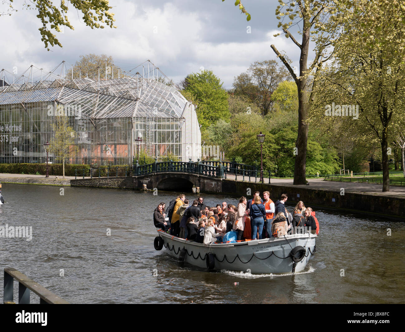 Botanical Garden and boats on Nieuwe Herengracht on kings day,   Amsterdam, Province North Holland, Netherlands - Stock Image