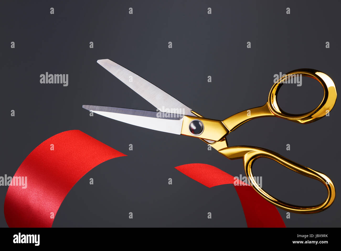 Golden scissors cutting red ribbon/ tape - Stock Image