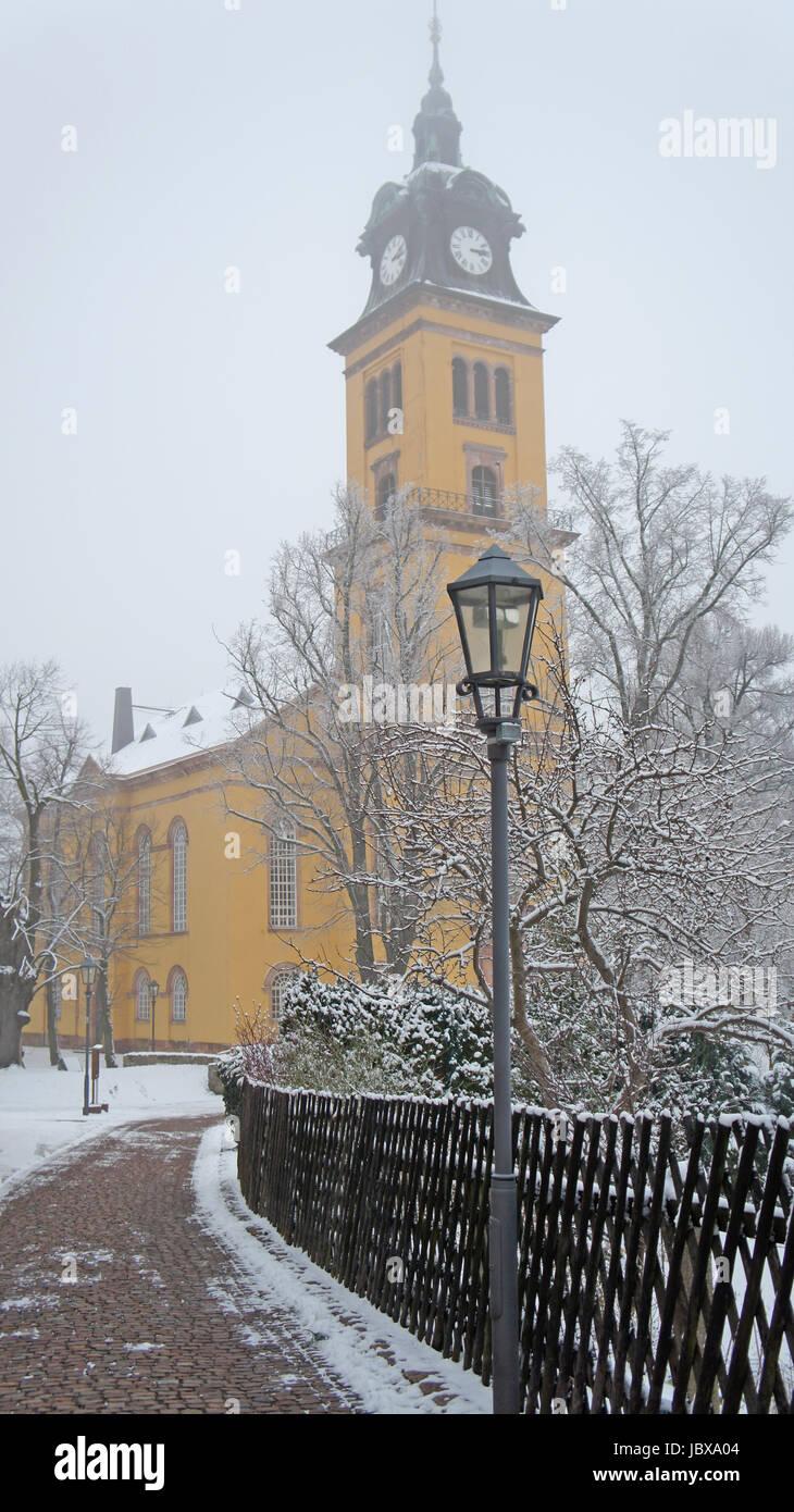 Eine Kirche im Erzgebirge in Sachsen an einem grauen Wintertag, gelbes Gebäude, Weg mit Laterne und kahle Bäume Stock Photo