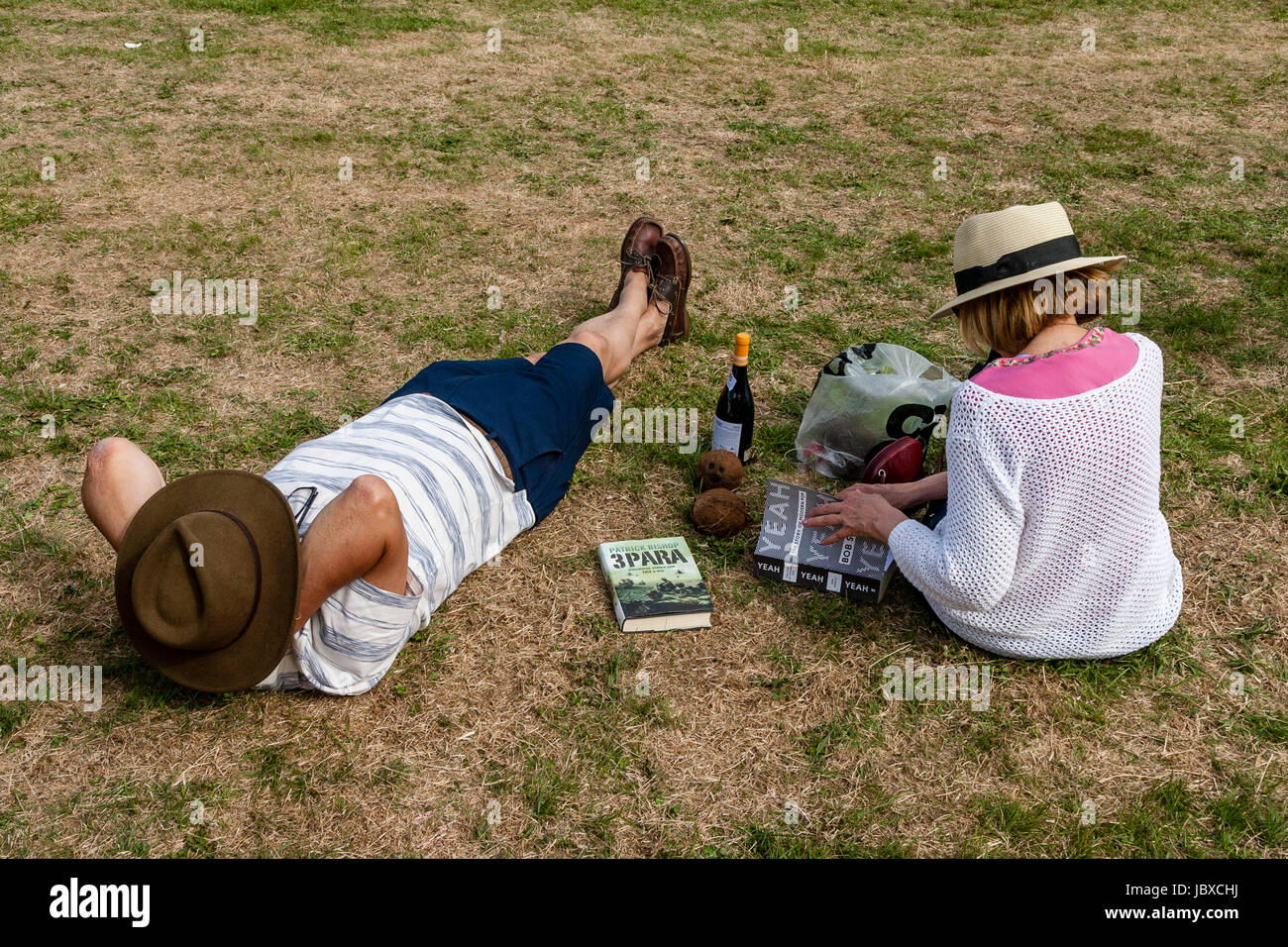 A Couple Relax On The Rectory Field At The Jevington Fete, Jevington, East Sussex, UK - Stock Image
