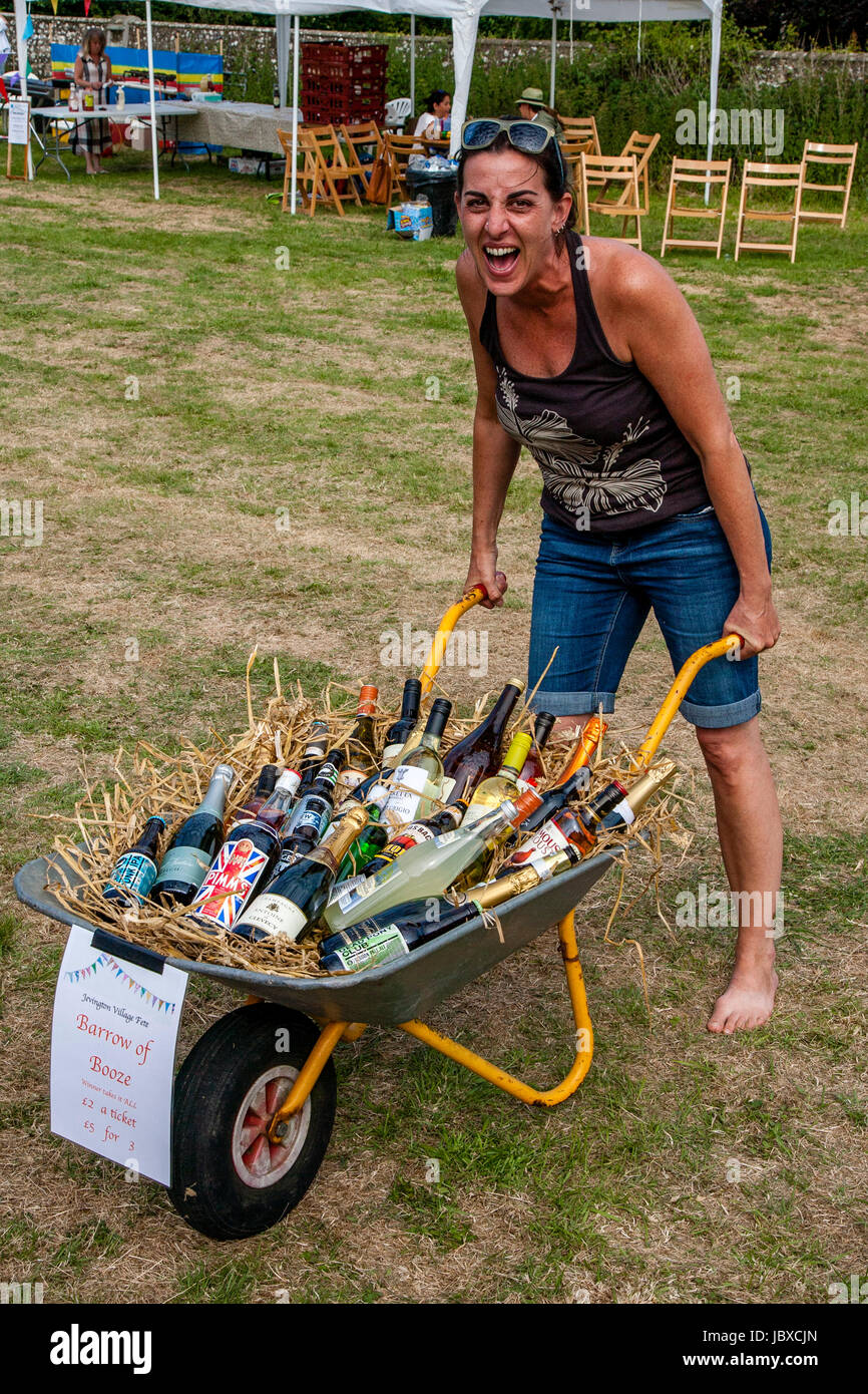 A Woman Wins The 'Barrow of Booze' At The Jevington Fete, Eastbourne, Sussex, UK Stock Photo