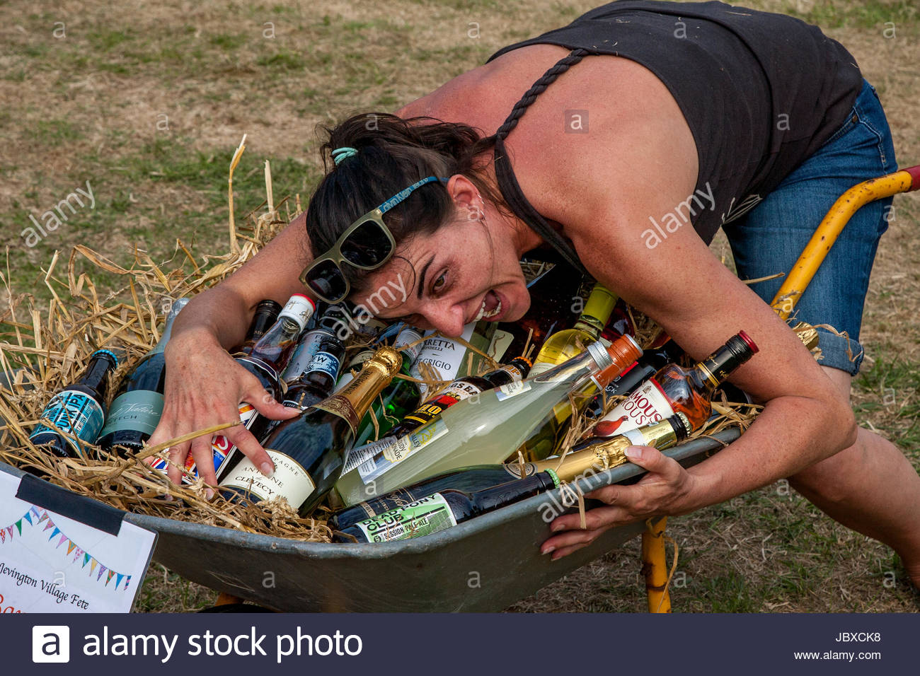 An Excited Woman Wins The 'Barrow of Booze' At The Jevington Fete, Eastbourne, Sussex, UK - Stock Image