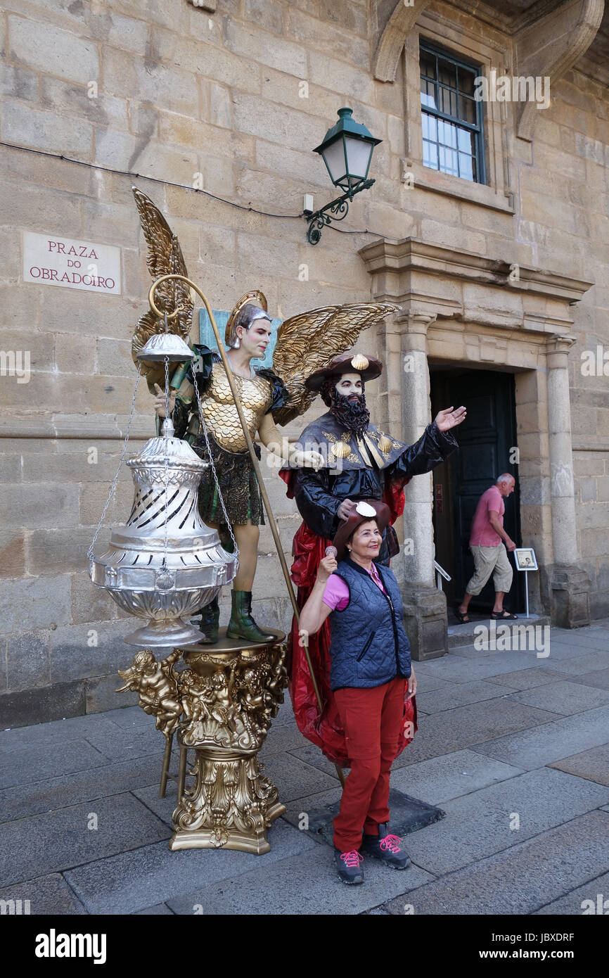Tourists posing with mime artists at Santiago de Compostela in Galicia Spain. - Stock Image