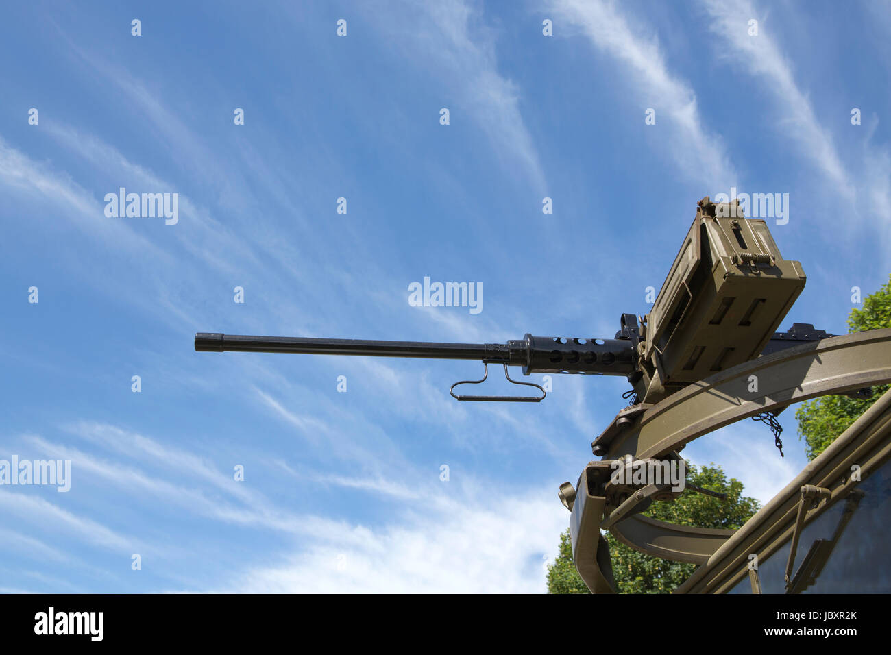 View looking up at a M2 Browning machine gun mounted on a scarff ring on top of a military truck. Blue sky and cloud - Stock Image