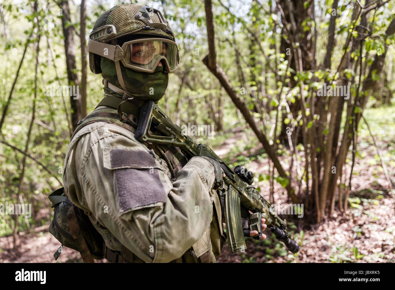 Officer in helmet on military intelligence at woods by day - Stock Image