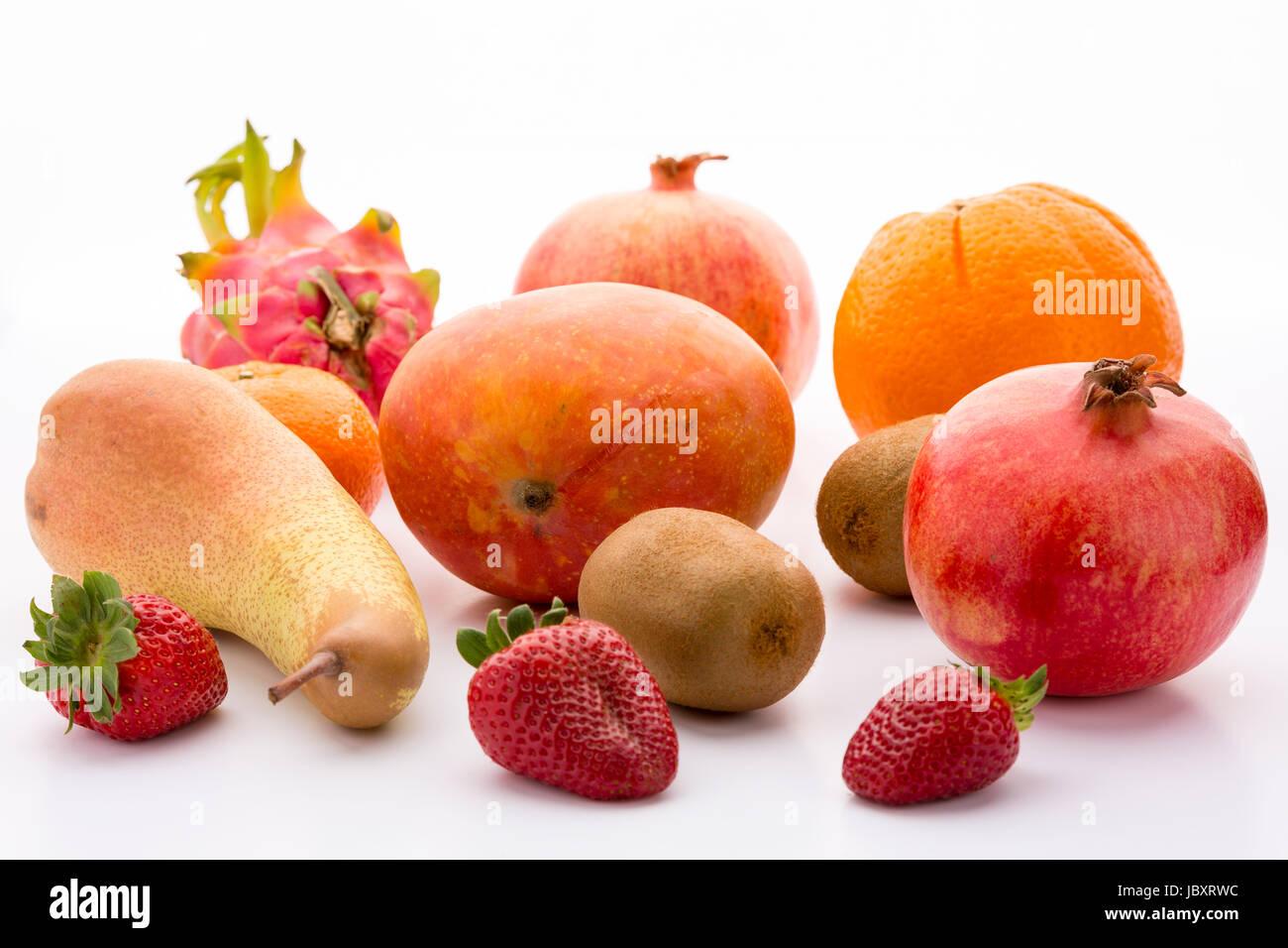 Exotic and domestic fruits: mango, two pomegranates, one pitaya, two kiwifruits, a pear, three garden strawberries - Stock Image