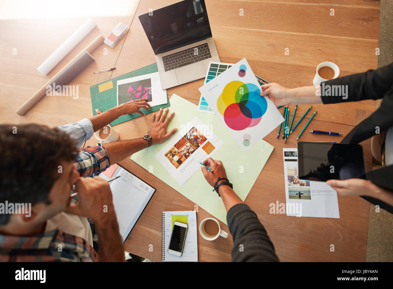 Top view shot of young designers discussing the color palette. Creative team brainstorming around table working - Stock Image
